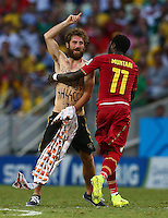 A pitch invader is led off by Sulley Muntari of Ghana