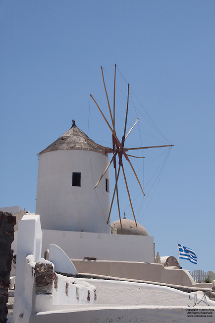 Windmill in Oia with Greek Flag