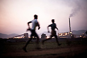 residents  of the Ijurupa village run past with an overview of the Vedanta Aluminum Refinery in Lanjigarh in the background in Orrisa, India.
