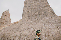 A Sumbanese man with traditional house in the background. Wainyapu, Kodi.