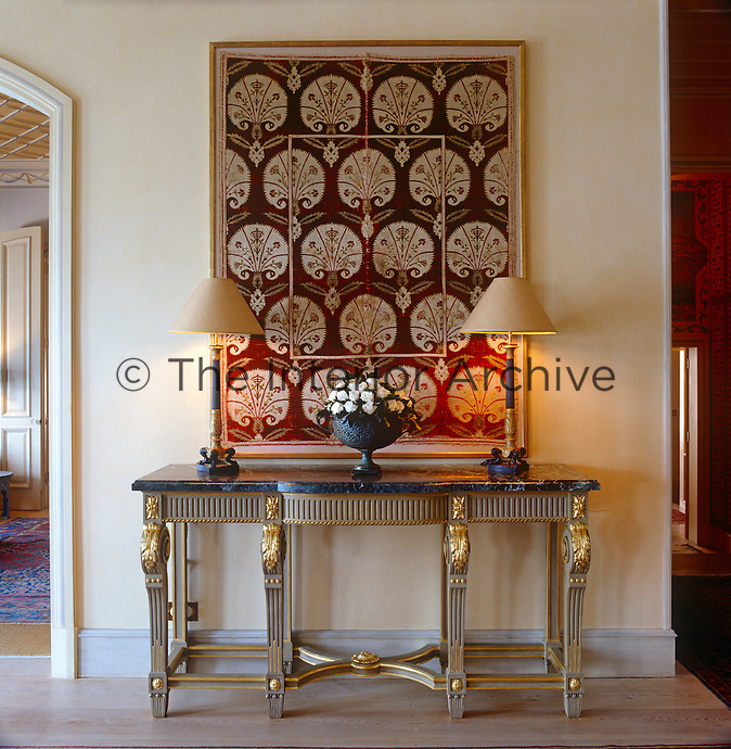 A marble-topped hall table with carved and gilded decoration stands below a framed panel of 17th century Ottoman cut velvet in the entrance hall