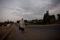 A woman walks at dawn on the main road of Shashamane, a village that hosts more than 300 Rastafarians Families, in Ethiopia on Wednesday March 19 2008.///..The Rastafarians, who are mainly from Jamaica, started migrating to Ethiopia 45 years ago, when Haile Selassie, whom they consider to be God incarnate, gave them 500 hectares of land on which to settle..Since the first 12 Jamaican settlers in 1963, the community has grown to over 200 families..The Rastafarian community insists that a mass exodus of Jamaicans to Ethiopia would not be a burden, despite the poverty and economic difficulties faced in the country..Some of them are skilled tradesmen such as carpenters and builders..Others are shop owners and they say that over the decades they have played an important role in the development of Shashamene..In January 2005 there were reports in the media that Bob marley's remains were to be exhumed and then reburied at Shashamane. His wife Rita Marley described Ethiopia as his spiritual home, provoking controversy in Jamaica, where his remains lie..At the beginning of the following month, thousands of fans gathered in Shashamane for a month of celebrations for what would have been Marley's 60th birthday. Until 2005 his birthday celebrations were always held in Jamaica. These events brought Shashamane to wider prominence throughout the world..