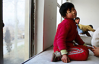 CHINA. Beijing. A young orphan in an orphanage outside of Beijing. 2007. The orphanage is a mix of orphans and children left for long periods of time by migrant workers who cannot take their children with them. There are currently millions of orphans in China living in orphanages spread throughout the country. As a result of China's one-child policy, many children are abandoned or given up if they suffer from any physical or mental handicap as the parents strive to have a child born 'normal' and well. This has led to may children being abandoned to live in state and privately-owned orphanages.