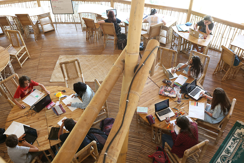 Birds eye view looking down onto a study period on the first floor of Heart of School. All floors and furniture made from bamboo<br /><br />The Green School (Bali) is one of a kind in Indonesia. It is a private, kindergarten to secondary International school located along the Ayung River near Ubud, Bali, Indonesia. The school buildings are of ecologically-sustainable design made primarily of bamboo, also using local grass and mud walls. There are over 600 students coming from over 40 countries with a percentage of scholarships for local Indonesian students.<br /><br />The impressive three-domed &quot;Heart of School Building&quot; is 60 metres long and uses 2500 bamboo poles. The school also utilizes renewable building materials for some of its other needs, and almost everything, even the desks, chairs, some of the clothes and football goal posts are made of bamboo.<br /><br />The educational focus is on ecological sustainability. Subjects taught include English, mathematics and science, including ecology, the environment and sustainability, as well as the creative arts, global perspectives and environmental management. This educational establishment is unlike other international schools in Indonesia. <br /><br />Renewable energy sources, including solar power and hydroelectric vortex, provide over 50% of the energy needs of the school. The school has an organic permaculture system and prepares students to become stewards of the environment. <br /><br />The school was founded by John and Cynthia Hardy in 2008.