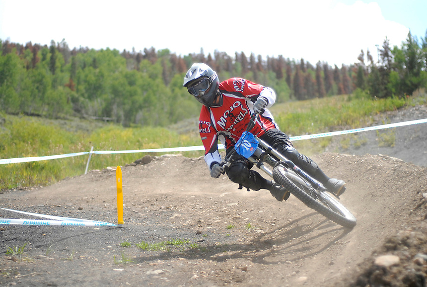 A downhill racer takes a bermed corner practicing for a downhill mountain bike race at Sol Vista ski area in Colorado in October, 2007.