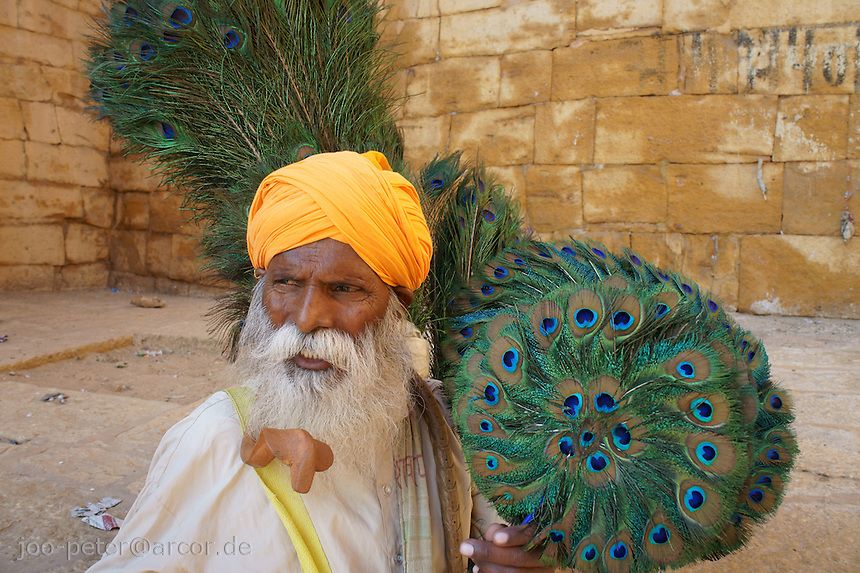 Man wearing saffron-coloured turban of Rajputs sells peacock feather items in the inner court between main gates of Jaisalmer Fort, Rajastan, India. Peacock feathers are attributs of Krishna, Vishnu and of importance in Jain religion. Inisde Jaisalmer Fort are seated seven Jain temple from 12th to 15th century.
