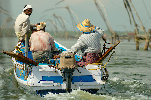 India, Kerala, backwaters. Indian men on a motor baot in the backwaters between Kollam to Allepey. No releases available.