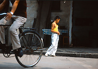 Cina, un ragazzo con maglia gialla e in primo piano una bicicletta <br />