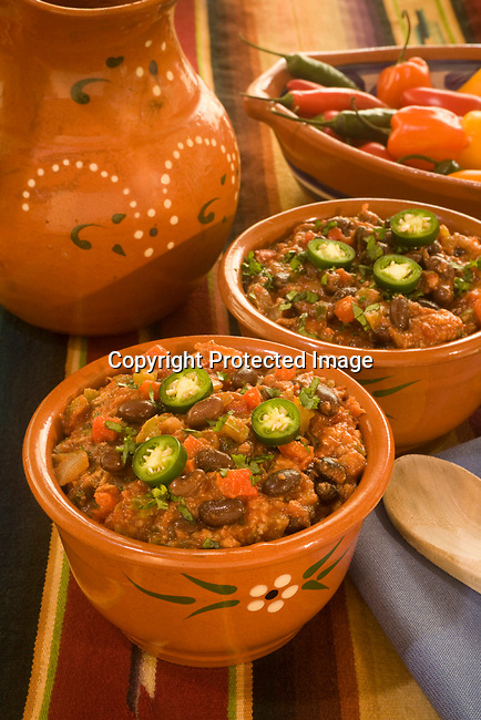 Black bean chili with cilantro and peppers with shallow depth of field.