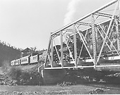 D&amp;RGW #483 leading eastbound passenger train with caboose at head end, crossing pin connected truss bridge over river.<br /> D&amp;RGW