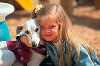 Portrait of a smiling young girl with her dog, a whippet.
