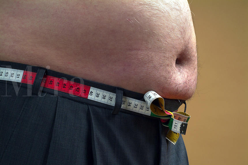 Obese mans tummy with tape measure. (UK) (r