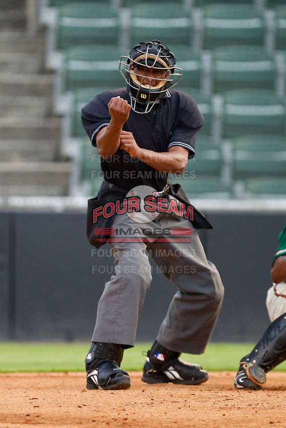 Home plate umpire Ramon DeJesus makes a strike call during a South Atlantic League game between the Greensboro Grasshoppers and the Kannapolis Intimidators at Fieldcrest Cannon Stadium August 2, 2010, in Kannapolis, North Carolina.  Photo by Brian Westerholt / Four Seam Images