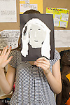 Education Middle School grade 8 art activity cut paper self portraits girl holding up art work to cover her face vertical