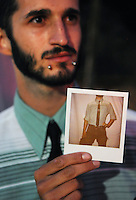 "Wesley Dawson of Seattle holds a Polaroid photo depicting the striped shirt, necktie and belt he wore to the 2011 Bumbershoot music and arts festival in Seattle Center on Monday, September 5, 2011. ""Ever since I got these lip piercings, I feel like I can wear fancier clothes and people won't think I'm a square,"" Dawson said."