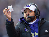 Husky defensive coordinator Jimmy Lake asks the ref if he wants his hand warmer back.