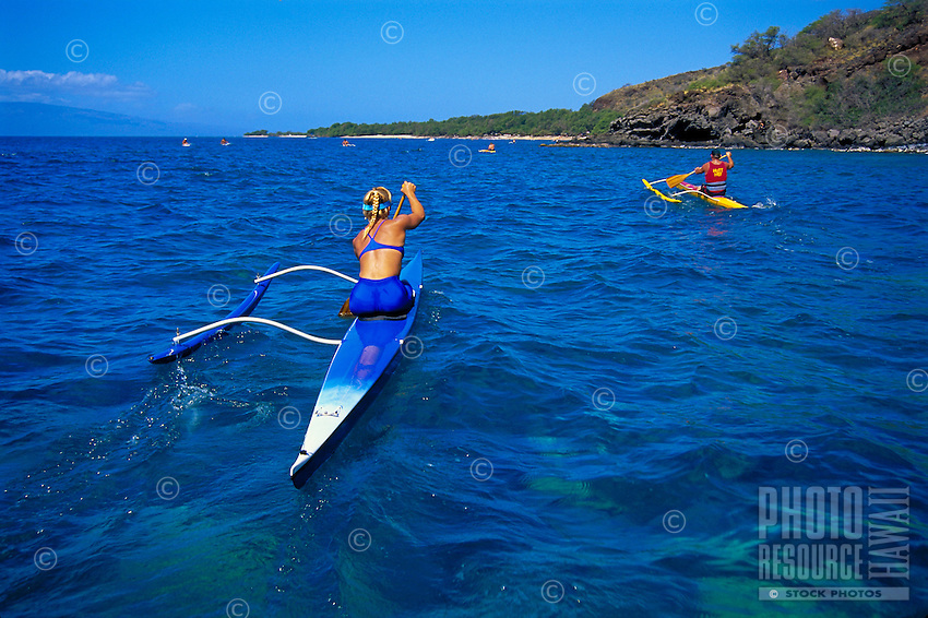 Two paddlers race in the beautiful blue waters off Maui in the annual Maui Kayak Club Pali race.