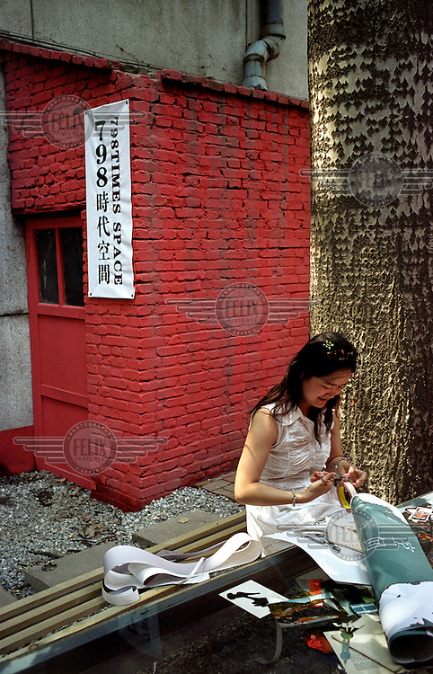 A plastic artist works outside her atelier in the Dashanzi Art District (also known as Factory 798). Many buildings in the former industrial area have been recently converted into fashionable art studios and galleries.