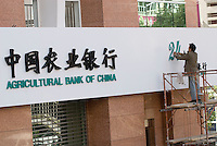 A man adds a sign for 24-hour banking at the Agricultural Bank of China, in Kunming, Yunnan Province.  As China's bank reform and modenize 24-hr banking is one amany services that are being offered to the increasingly wealthy public..29 Nov 200
