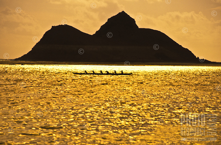 Group paddling outrigger canoe in open ocean at sunrise in Lanikai, Windward Oahu with Moku Lua island in rear