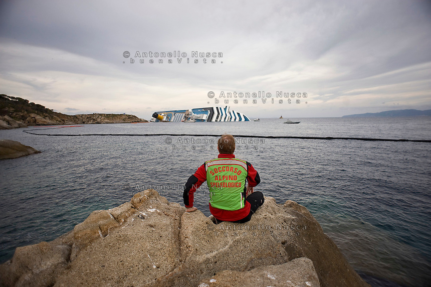 Isola del Giglio, Italy, January 19, 2012. A rescuer look at the Costa Concordia aground in front of the harbour of the Isola del Giglio (Giglio island) after hitting underwater rocks.
