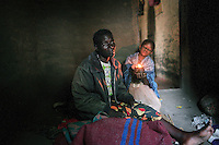 MPHANDULA, MALAWI - AUGUST 21: Ethel Dailesi, age 44, sits in her bedroom with her daughter Rebecca Masawo, age 10, on August 21, 2006 in Mphandula village, about 30 miles outside Lilongwe, Malawi. Ethel was diagnosed with HIV/Aids in 2004 and has been on antiretroviral drugs since December 2005. She has just taken her medicine. She is often sick and her two daughters take care of her. Her children cook and clean for her. The girls attend a school nearby but they usually stay home when their mother is too sick. Mphandula is a poor village in Malawi, without electricity or clean water. Nobody owns a car or a mobile phone. Most people live on farming. About 7000 people reside in the village and the chief estimates that there are about five-hundred orphans. Many have been affected by HIV/Aids and many of the children are orphaned. A foundation started by Madonna has decided to build an orphan center in the village through Consol Homes, a Malawi based organization. Raising Malawi is investing about 3 million dollars in the project and Madonna is scheduled to visit the village in October 2006. Malawi is a small landlocked country in Southern Africa without any natural resources. Many people are affected by the Aids epidemic. Malawi is one of the poorest countries in the world and has about 1 million orphaned children. (Photo by Per-Anders Pettersson)