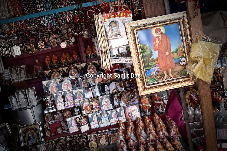Small memoribilia of Sai Baba is sold in a stall outside the Prasadalaya in Shirdi, Maharashtra, India. The Sai Prasadalaya, feeds an approximate number of 30000 Sai Baba devotees as a Prasad (holy meal) everyday. Free Prasad meals are served to all the devotees. An approximate number of 1000 devotees are served everyday with this facility. Expenses for a plate of Prasad meal  is around Rs. 15/- but the Saibaba Sansthan provides prasad meals to all Sai devotees to Rs. 6/- only. The prasadalaya at the Shirdi Sai Baba Shrine is powered by a large array of concave mirrors that transform sunlight to energy to create hot water and steam for the cooking process. Photograph: Sanjit Das