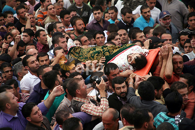 Palestinians carry the body of a Hamas militant Mamoun al-Natsha during his funeral in the West Bank city of Hebron, Friday, Oct. 8, 2010. Israeli troops killed two senior Hamas militants in an early-morning raid in the city on Friday, the Israeli military and Hamas officials said, raising tensions as peace talks remain stuck over the issue of Israeli settlements. The two gunmen were wanted for involvement in the killing of four Israelis near Hebron on Aug. 31, just as new Israeli-Palestinian peace talks were getting under way, the Israeli military said. Media aligned with Hamas in the Gaza Strip, which Hamas controls, also said the men were behind the attack Photo by Najeh Hashlamoun