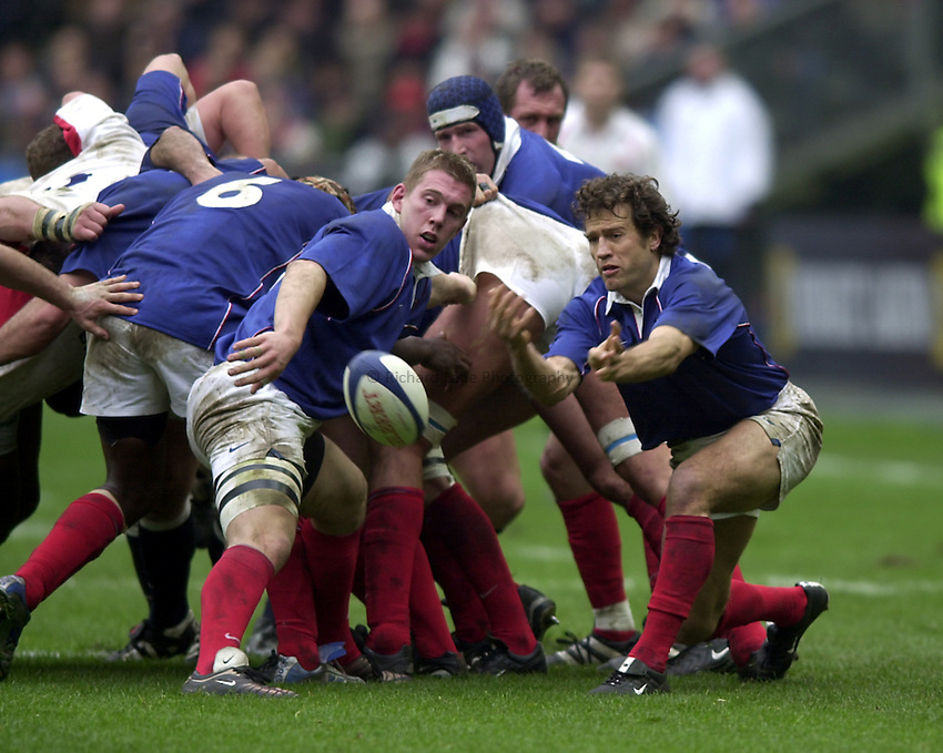 Photo.Richard Lane.France v England at Stade de France. 2-3-2002. Lloyds TSB Six Nations Championship..Fabien Galthie gets the ball away as Imanol Harinordquy looks on.