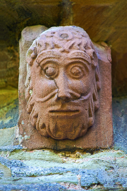 Norman Romanesque exterior corbel no 61 - sculpture of  a human head with curly hair and beard. The Norman Romanesque Church of St Mary and St David, Kilpeck Herefordshire, England. Built around 1140