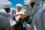 Gouro, Chad. In the northern Tibesti region of Cha, men shake hands in ritual after first prayer service to celebrate Eid al-Fitr, the end of Ramadan.