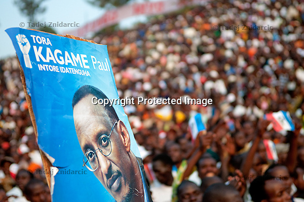A poster of Rwandan president Paul Kagame is lifted above his supporters during a presidential campaign rally in Nyaruguru District, Rwanda.