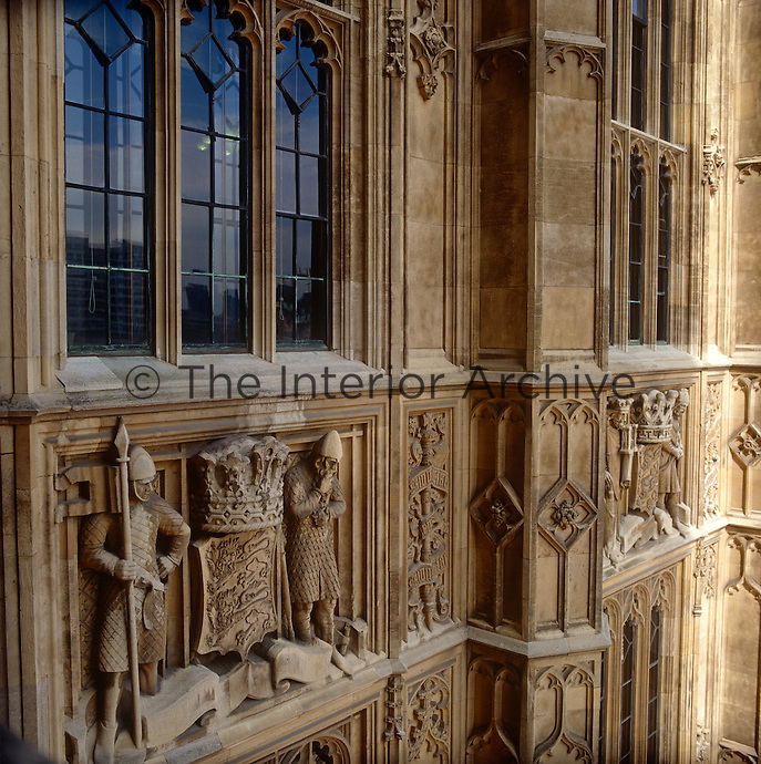 Two knights peer down from their lofty spot on the ornately carved exterior of the House of Lords