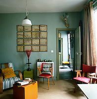 The blue sitting room has a retro feel with a variety of red and blue seating simply arranged.