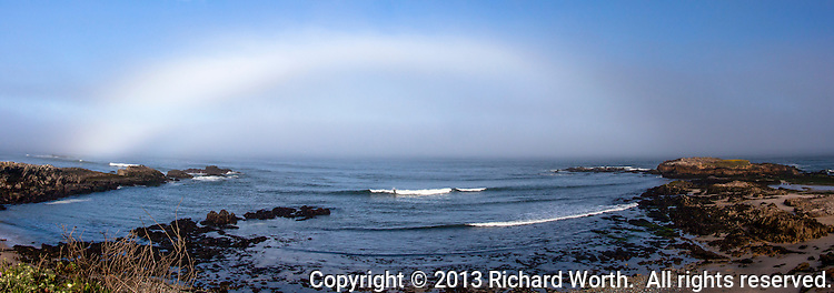 Fog off shore and the angle of morning light combined to create a bow over the ocean at Pescadero State Beach on California's coast.