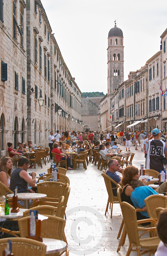 The main street Stradun Placa with traditional houses and flocks of tourists, view over outside seating cafe with people towards the city gate and Franciscan's church tower Dubrovnik, old city. Dalmatian Coast, Croatia, Europe.