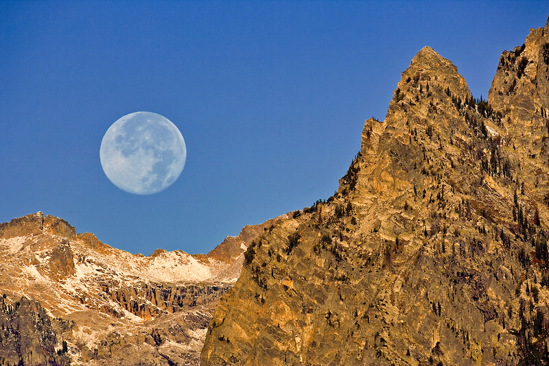 Full moonset over Teton Mountains. Grand Teton National Park, WY