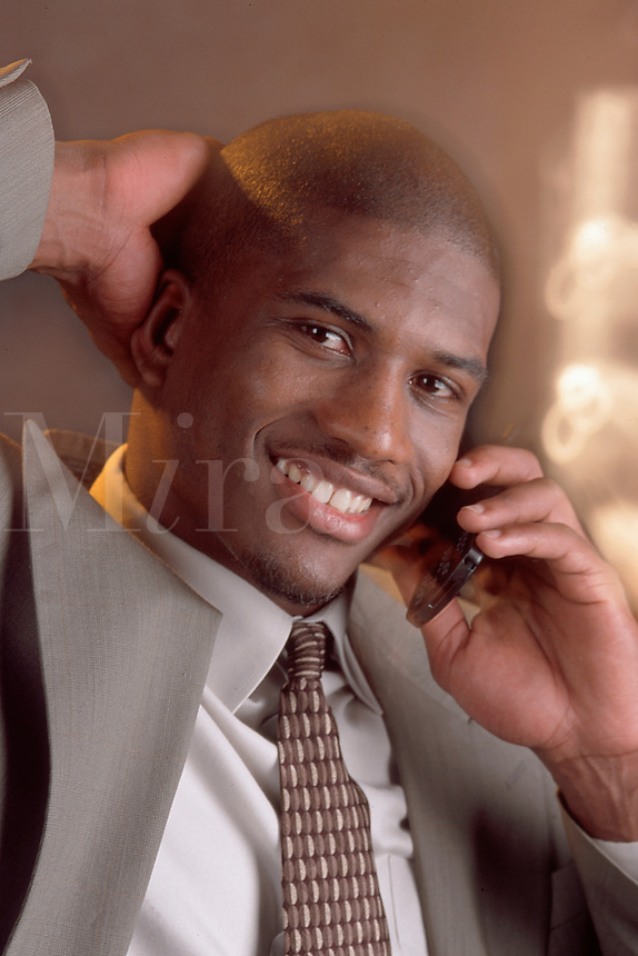 A smiling African American man talking on the telephone.