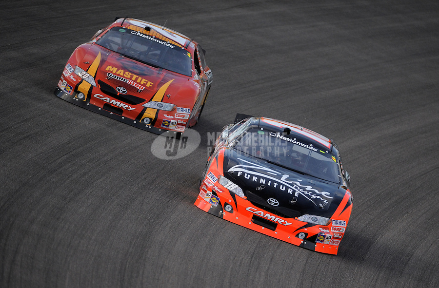 Nov. 20, 2010; Homestead, FL, USA; NASCAR Nationwide Series driver Kyle Busch (right) leads Joey Logano during the Ford 300 at Homestead Miami Speedway. Mandatory Credit: Mark J. Rebilas-