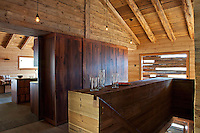 The walls of the chalet are lined with a mixture of new and recycled pine, a rustic staircase descending from the kitchen/dining area which now occupies the former hayloft