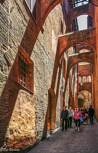 Visitors explore a shadowed arched alleyway, Siena, Italy.