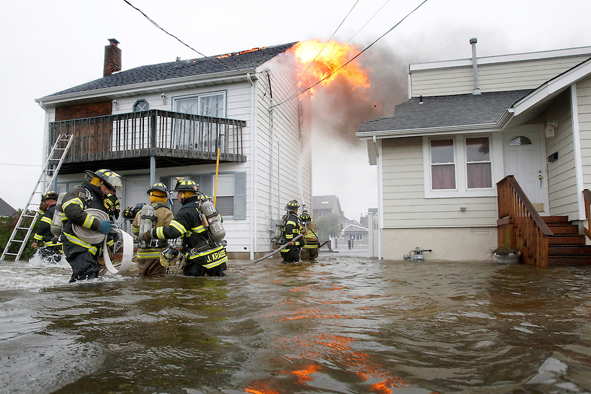 Manasquan firefighters wade through nearly waist deep water as they battle a house fire on Brielle Road just after 8 am as Hurricane Irene hits the Jersey Shore.   (8/28/2011)  Andrew Mills/The Star-Ledger