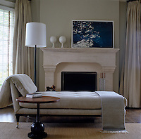 A contemporary chaise longue in the bedroom stands infront of a stone fireplace on which is a photograph by Nan Goldin