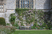 A wooden bench next to a summer border in the Lower Garden at Haddon Hall