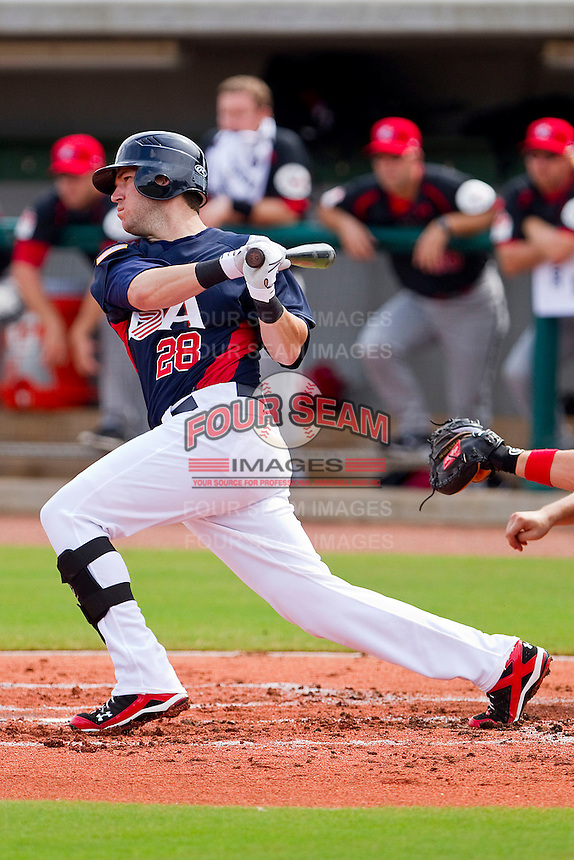 Chad Tracy #28 of the United States World Cup/Pan Am Team follows through on his swing against Team Canada at the USA Baseball National Training Center on September 28, 2011 in Cary, North Carolina.  (Brian Westerholt / Four Seam Images)