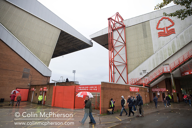 A match programme seller standing in the rain between the Brian Clough Stand (left) and the Trent End at the City Ground, Nottingham before Nottingham Forest take on visitors Ipswich Town in an Npower Championship match. Forest won the match by two goals to nil in front of 22,935 spectators.