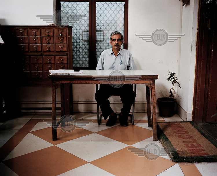 A librarian sits at his desk in the Delhi Public Library in Old Delhi.