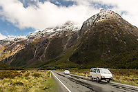 Vehicles pass below the high peaks of Milford Sound on the South Island of New Zealand.