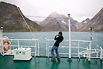 A young man braces himself against he Katabatic winds in Greenland's Prins Christian Sound. The young man is a student and part of the Cape Farewell Youth Expedition that was organized by the British Council of Canada.