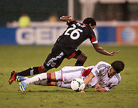 Stephen McCarthy (15) of the New England Revolution is fouled by Lionard Pajoy (26) of D.C. United during a Major League Soccer game at RFK Stadium in Washington, DC.  New England defeated D.C. United, 2-1.